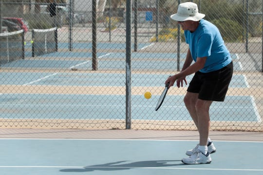 """A man plays pickleball at DeMuth Park in Palm Springs, Calif. on Monday, March 16, 2020 after Gov. Gavin Newsom """"strongly encouraged"""" the 65-and-older population to practice home isolation to prevent the spread of coronavirus."""