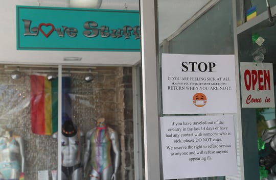 A sign tells shoppers to stay out if they are sick or have traveled recently at Love Stuff in downtown Palm Springs, March 16, 2020.