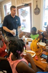 Owner TJ Zoltak serves a table at East Hill Pizza on 12th Avenue in Pensacola on Monday, March 16, 2020.  The restaurant is offering free lunch to students 13 years old and younger who are out of school due to the coronavirus closings.