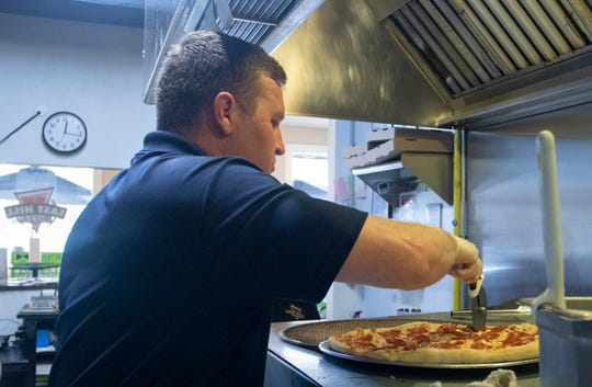 Owner TJ Zoltak slices pizza at Hill Pizza on 12th Avenue in Pensacola on Monday, March 16, 2020.  The restaurant is offering free lunch to students 13 years old and younger who are out of school due to the coronavirus closings.