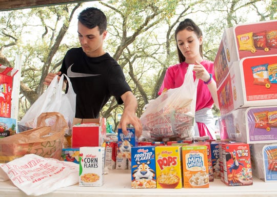 From left, Tate High School student Kaleb Rudd, 16, and Ransom Middle School student Audrey Rudd, 13, fill bags during a food distribution event organized by the Cantonment Improvement Committee at Carver Park in Cantonment on Monday.