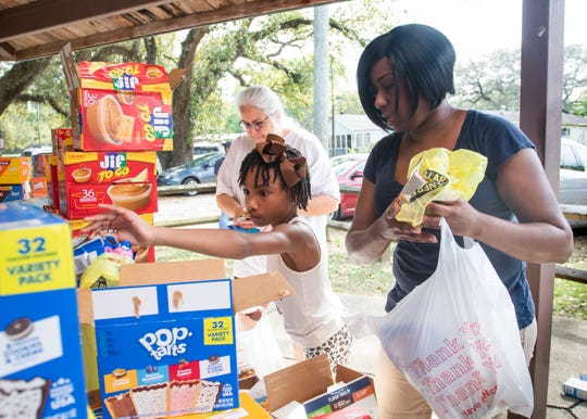 From right, Pamela Linzy, JaDora Linzy and Kathey Rudd fill bags during a food distribution event organized by the Cantonment Improvement Committee at Carver Park in Cantonment on Monday.