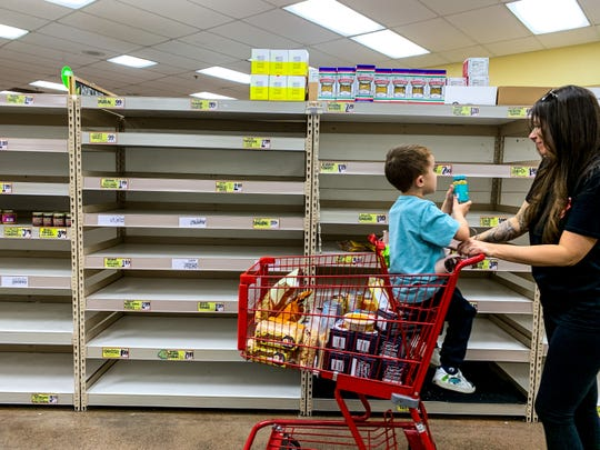 A shopper walks by empty pasta shelves at Trader Joe's at Camelback Colonnade on March 15, 2020 in Phoenix.