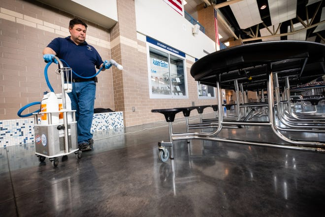 Scott Macpherson uses a Clorox 360 machine to disinfect tables after lunch period Friday, March 13, 2020, at Marysville High School. The machine uses an electrostatic fog that was approved to kill COVID-19 to disinfect surfaces.