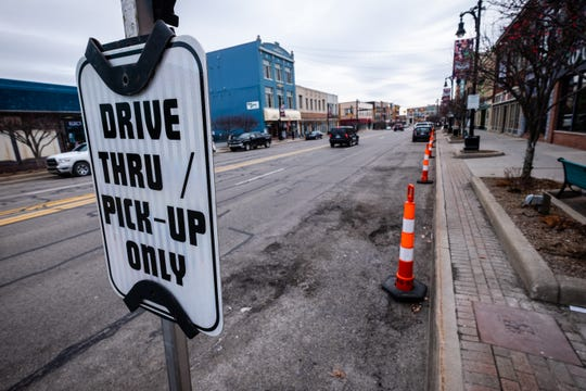 Traffic cones block parking spots in front of restaurants along Huron Avenue Monday, March 16, 2020, in downtown Port Huron. After all restaurants were ordered to close to dine-in business, cones were set out in front of businesses to create easy access for take-out orders.