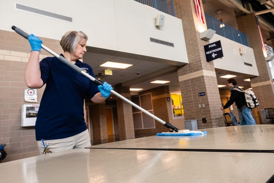 A student walks past Jill Roehl, left, as she disinfects the surface of a table after lunch period Friday, March 13, 2020, at Marysville High School. On March 12, Gov. Gretchen Whitmer ordered all K-12 schools in Michigan be closed starting Monday, and to remain closed through April 5.