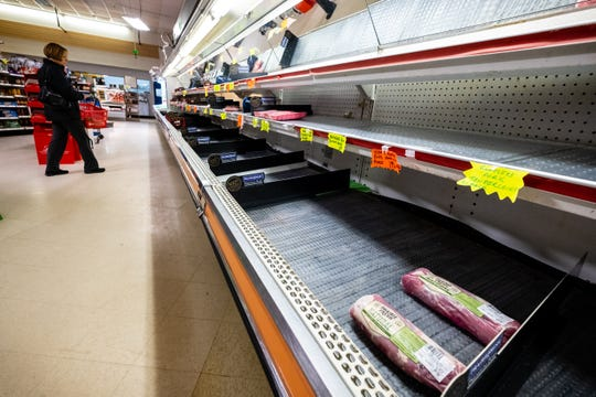 A shopper walks past a barren meat section Friday, March 13, 2020, at Wally's Supermarket in Marysville. Janet Lockwood, who works in the store's deli, said meats were selling almost as fast as they were being stocked.