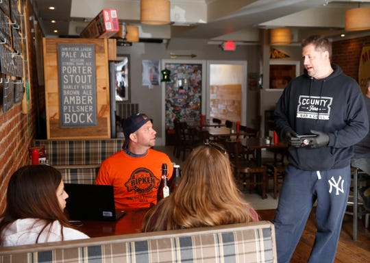 Dana Tompkins, owner of County Fare in the Village of Wappingers Falls talks with patrons on March 16, 2020.