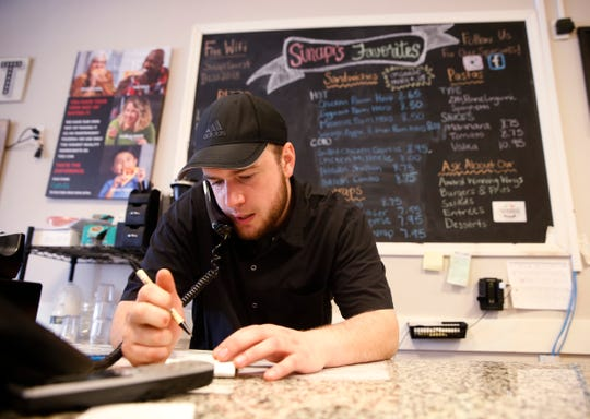 Peter Sinapi takes a phone order at Sinapi's Pizza in the Town of Poughkeepsie on March 16, 2020.