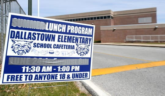 Summer lunch program signs are modified with duct tape to announce the Coronanvirus emergency school lunch program at Dallastown High School Monday, March 16, 2020. The school district is offering grab-n-go meals to students weekdays from 11:30 a.m. to 1 p.m. during the emergency. Bill Kalina photo