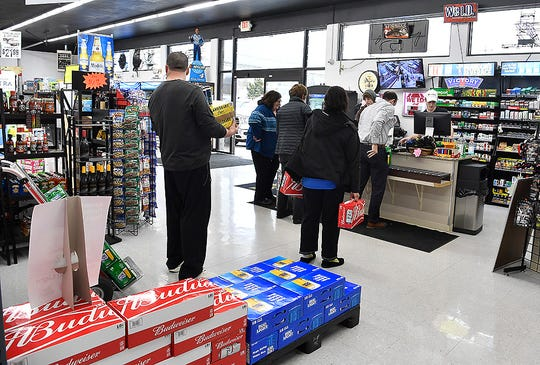 """Customers wait in line to check out at Brandon's Beverage on Mt. Rose Avenue in Springettsbury Township, Monday, March 16, 2020. A sign on the door reads """"We are considered essential, We will be open"""" John A. Pavoncello photo"""