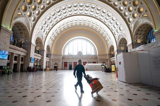 Washington Union Station, a major transportation hub in the nation's capital, is nearly empty during morning rush hour as many government and private sector workers stay home during the coronavirus outbreak, in Washington, Monday, March 16, 2020. (AP Photo/J. Scott Applewhite)