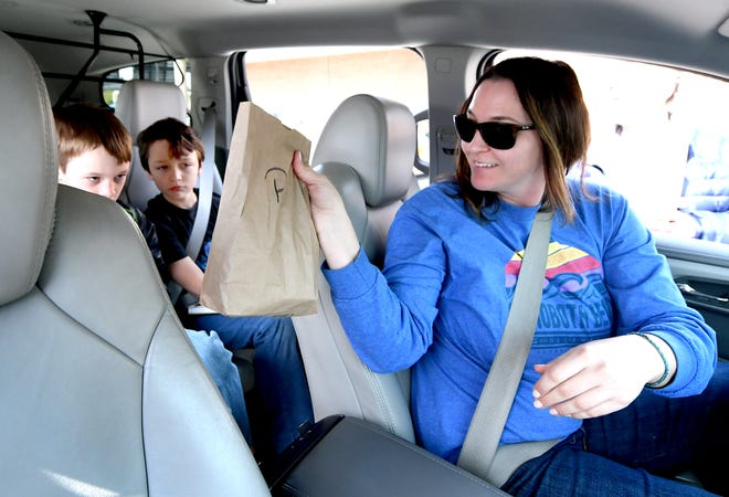 Layla Montagne hands a lunch to her son Holden Niebrugge, 8, after visiting the lunch program at Dallastown High School Monday, March 16, 2020. Montagne took her son and neighborhood friends Gavin Milhimes, 9, left, and his brother Colton, 6, along for the lunch pick up. The children are students at York Township Elementary School. The school district is offering grab-n-go meals for all students weekdays from 11:30 a.m. to 1 p.m. Bill Kalina photo