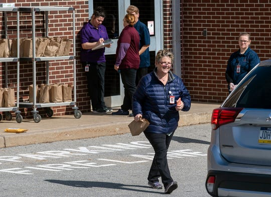 Susan Eckert, a cafeteria manager at Dallastown Area High School, brings a lunch out to a car on Monday.