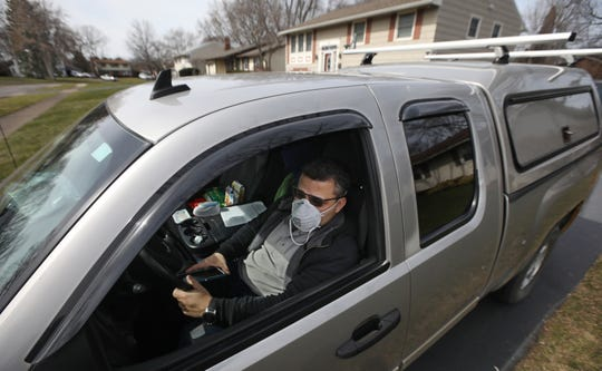 Victor Millan sits in his truck outside his Greece home Monday, March 16, 2020. Millan slept in his truck last night, after being told by Monroe County he needs to quarantine because he may have had contact at his job with a coronavirus carrier. Millan has an auto-immune child in his home so doesn't feel safe in there.
