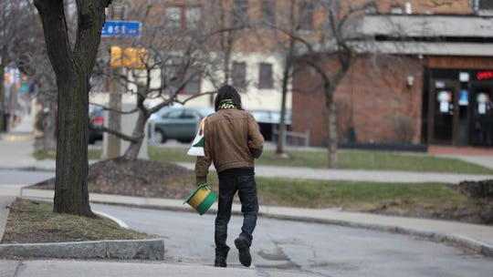 A lone St. Patrick's Day reveler heads towards East Avenue in downtown Rochester Saturday, March 14, 2020.  The parade was canceled due to the coronavirus pandemic.