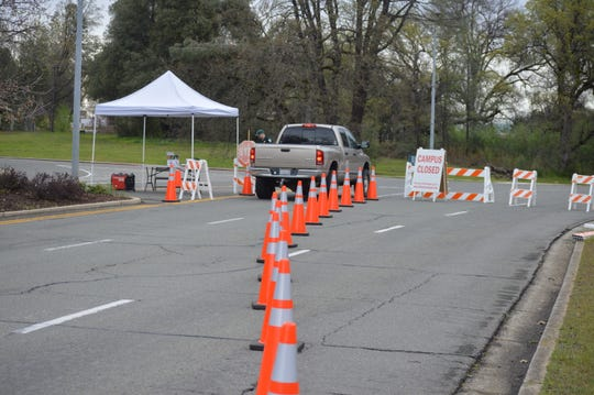 Shasta College campus police direct traffic at the campus' main checkpoint on March 16, 2020. Shasta College is one of three sites where a field medical station could be established.