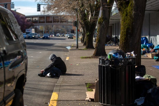 A man sits on a sidewalk outside of the Rite-Aid in downtown Salem on March 16, 2020.