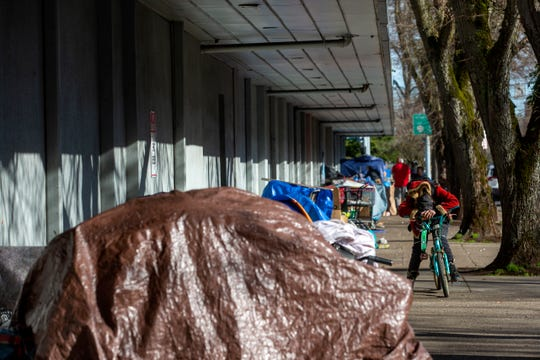 Belongings of those experiencing homelessness pile up on the sidewalk in downtown Salem on March 16, 2020.