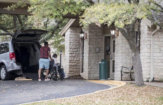 A person is escorted into Pflugerville Care Center on Friday. The nursing facility is restricting visitors to prevent the introduction of the new coronavirus to its residents.