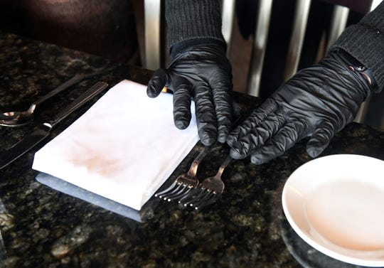 Traci Hoem wears plastic gloves as she sets tables on Monday, March 16, at Parker's Bistro in Sioux Falls. Hoem said this is a new precaution she is taking because of coronavirus concerns.