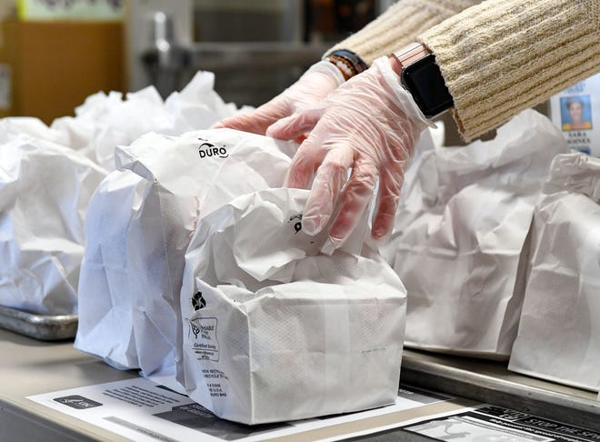 Sara Joines, child nutrition assistant, sets out lunch bags for students to receive while school is out of session due to concerns about the coronavirus on Monday, March 16, at Terry Redlin Elementary in Sioux Falls.