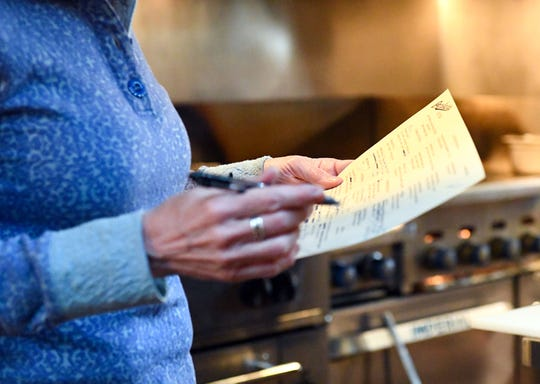 Stacy Newcomb Weiland makes notes on a menu on Monday, March 16, at Parker's Bistro in Sioux Falls.