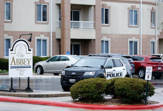 Police cars blocked the entrances to The Abbey apartment complex on Monday, March 16, 2020.