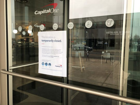 """A sign on the Capital One Cafe Monday, March 16, 2020  informs customers they closed because """"we have a role to play in supporting public health officials and government leaders in their efforts to contain they COVID-19 virus."""" The sign says there has not been a confirmed case """"in this location"""" and the closure is a proactive measure."""