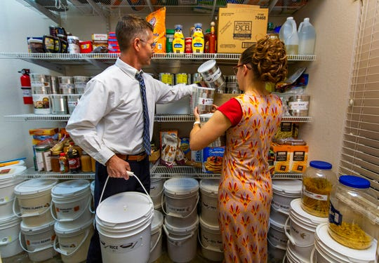 Cory, left, and Holly Steed sort through some of the food items stored in their home pantry on Monday, March 2, 2020 in Las Vegas. The Steeds are members of the Church of Jesus Christ of Latter-day Saints and follow its recommendations to maintain a supply of food, water and other provisions for use in an emergency. (L.E. Baskow/Las Vegas Review-Journal via AP)