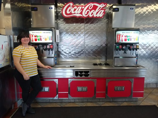 Jessica Jaime, a manager at the Carl's Jr. restaurant on Sunset Blvd. in St. George, stands in front of the beverage area where there are not any lids,straws or other items customers can touch in an effort to prevent coronavirus spread.