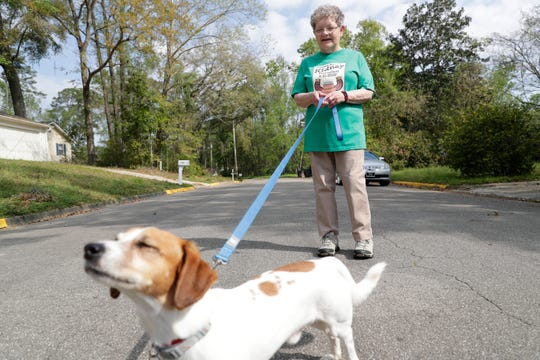 Dee Wilder walks her dog, Charlie, in her neighborhood Monday, March 16, 2020. After getting a kidney transplant in 2002, Wilder is immunosuppressed and must take extra precautions amid the COVID-19 pandemic.
