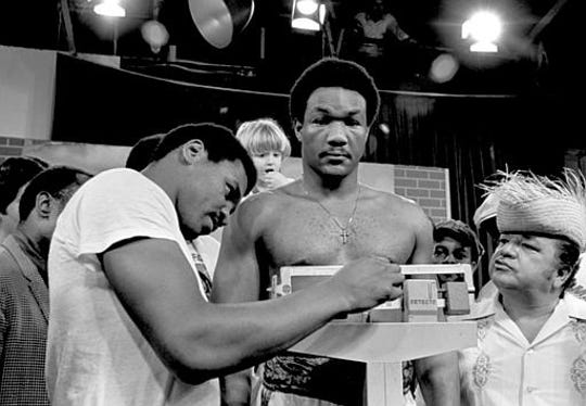 Heavyweight boxer Jimmy Young, left, looks over the scale as former champ George Foreman weighs in, in San Juan, P.R., March 16, 1977.  At right is San Juan TV personality Jose Miguel Agrelot, on whose show the weigh-in was held.  (AP Photo/Jim Bourdier)