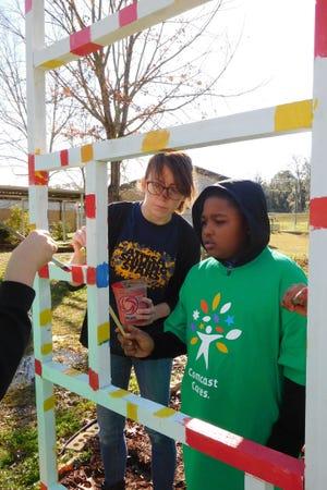 Art teacher Ashley Chandler helps a student paint the garden trellis.