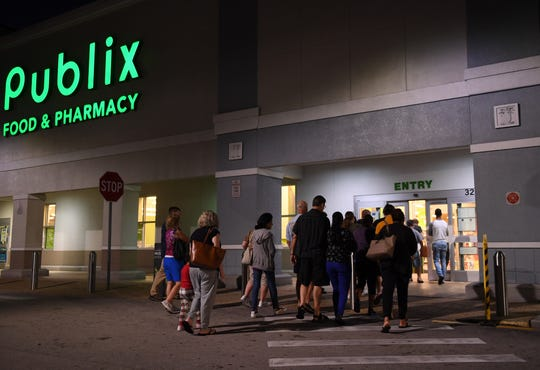 Early shoppers eagerly await the opening of Publix just before 7 a.m. March 16, 2020, on Darwin Square in Port St. Lucie.