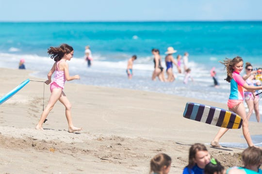 Friends Haylee Rudick (left), 8, and Neveah Wood, 8, both of Stuart, enjoy a sunny day at Stuart Beach on Monday, March 16, 2020, on Hutchinson Island. All Treasure Coast schools are closed through at least March 27 as communities take steps to stop the spread of the coronavirus.