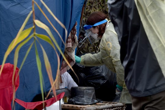 Krista Burns, a licensed vocational nurse with the Ventura County Health Care Agency, takes the temperature of a man at a homeless encampment In Santa Paula Creek on Monday, March 16, 2020.