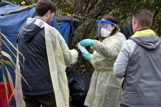 Licensed vocational nurse Krista Burns and Dr. John Nuhn, of the Ventura County Health Care Agency, put on protective gear as they prepare to help a patient at a homeless encampment in Santa Paula Creek on Monday, March 16, 2020. Nuhn and Burns were offering help with Ventura County's backpack medicine program when a man who wasn't feeling well fell down while talking to the group about his dizzy spells, fevers and dry cough.