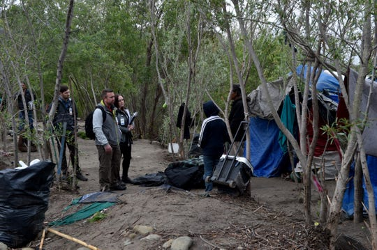 (From left) John Nuhn, Krista Burns and Zachary Zwolak, of the Ventura County Health Care Agency, speak with people at a homeless encampment in Santa Paula Creek on Monday, March 16, 2020. They are part of Ventura County's backpack medicine program, which offers services and health care to the homeless.
