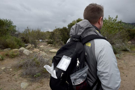 Dr. Zachary Zwolak, of the Ventura County Health Care Agency, carries a pack containing safety gear for treating potential COVID-19 patients as members of Ventura County's backpack medicine program offer help to people at homeless encampments near Santa Paula on Monday, March 16, 2020.