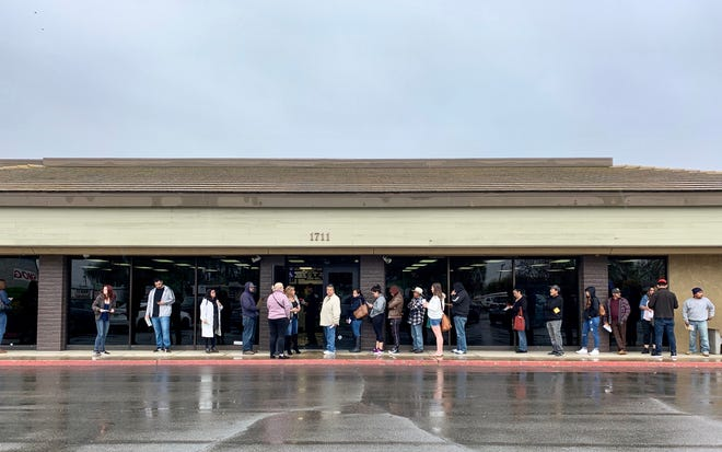 Customers wait in line outside at the Visalia Department of Motor Vehicles on Monday, March 16, 2020. Workers at the office let people in one or two at a time to conduct their business.