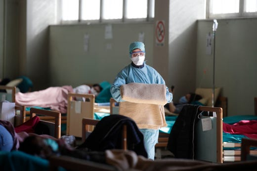 Medical staff work at one of the emergency structures that were set up to ease procedures at the Brescia hospital in northern Italy, March 16, 2020.