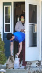Amy Driscoll looks on from inside her house as son Cade, 14, grabs food dropped off by her friends.