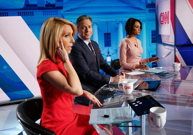 CNN news anchor Jake Tapper, flanked by Univision's news anchor Ilia Calderón, right, watches as co-anchor Dana Bash adjusts her earpiece before the start of the 11th Democratic Party 2020 presidential debate in a CNN Washington Bureau studio in Washington, D.C., on March 15, 2020.