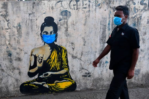 A resident wearing a face mask amid concerns over the spread of the COVID-19 novel coronavirus walks past a graffiti of Buddha wearing face mask, in Mumbai on March 16, 2020.