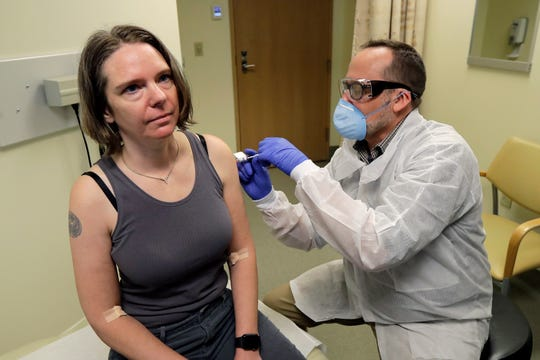 A pharmacist gives Jennifer Haller, left, the first shot in the first-stage safety study clinical trial of a potential vaccine for COVID-19, the disease caused by the new coronavirus,, March 16, 2020, at the Kaiser Permanente Washington Health Research Institute in Seattle.
