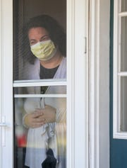 Amy Driscoll, 48, looks out her front door Sunday after testing positive for COVID-19.