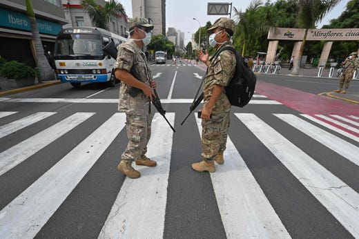 Peruvian army soldiers control traffic in Lima on March 16, 2020, in an attempt to persuade the population to stay at home, one day after President Martin Vizcarra announced a State of Emergency and a two-week nationwide home-stay quarantine together with the closure of all borders to fight the spread of the novel COVID-19 coronavirus.  No fatalities have been recorded of the 86 cases of Covid-19 detected in the country.