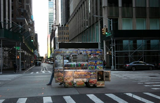 A food truck vendor pushes his cart down an empty street near Times Square in New York, on Sunday, March 15, 2020.