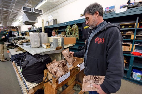 Owner Jeff Zaglin stocks MRE meals for sale at the Greenville Army Store Monday, March 16, 2020, in Greenville, S.C.